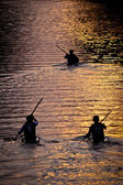 3 canoeists going up the canal during sunset, early spring — Stock Photo