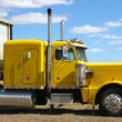 Yellow truck against blue sky - Stockfoto