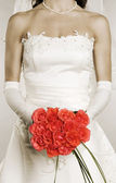 Woman in wedding dress with bunch of roses — Stock Photo