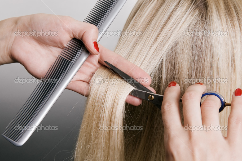 Hairdresser cutting blonde hair. closeup over grey background — Stock Photo #5099509