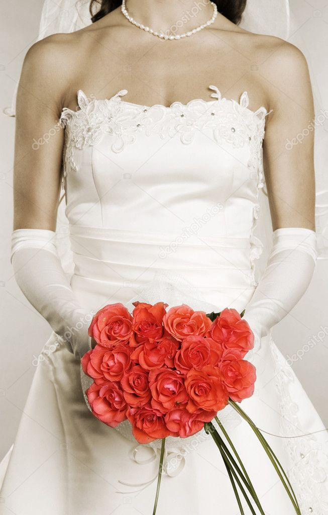 Elegant woman in wedding dress with bunch of roses