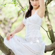 Brunette in white dress sitting — Stock Photo