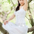 Brunette in white dress sitting — Stock Photo #5156778