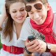 Royalty-Free Stock Photo: Smiley teenagers looking at cellphone