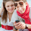 Smiley teenagers looking at cellphone - Foto de Stock