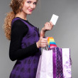 Smiley girl with credit card and paper bags — Stock Photo