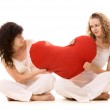 Two girls pulling red heart — Stock Photo