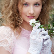 Beautiful young woman in white gloves with flowers — Stock Photo