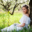 Stock Photo: Woman in white dress sitting on grass