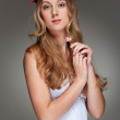 Beautiful young woman with small flower — Stock Photo