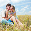 Happy young couple against blue sky - Stock Photo