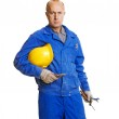 Serious worker holding his hardhat and different tools — Stock Photo