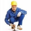 Workman sitting on the floor and holding gripping tongs — Stock Photo #5159395