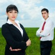 Serious businesspeople standing on green meadow — Stock Photo