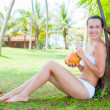Attractive woman sitting near the palm — Stock Photo