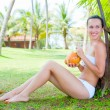 Stock Photo: Attractive woman sitting near the palm