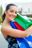 Happy woman with her purchases — Stock Photo
