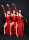 Three dancers in red evening gown — Stock Photo