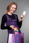 Happy woman with credit card and bags — Stock Photo