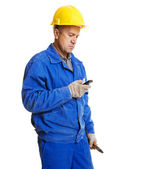 Worker reading message in his mobile phone — Stock Photo