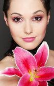 Jovem mulher atraente com lírio rosa — Fotografia Stock