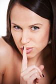 Alluring woman with forefinger over mouth — Stock Photo