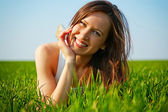 Attractive young woman lying in green grass — Stock Photo