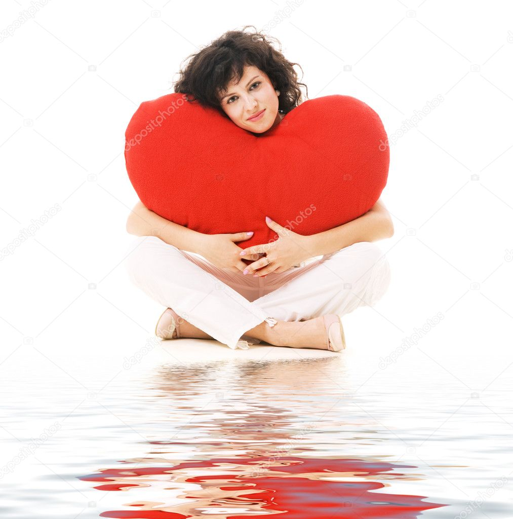 Happy young woman with big red heart sitting against white background  Stock Photo #5157432