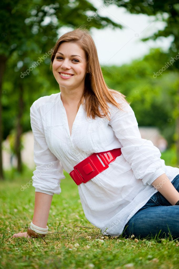 Beautiful young woman sitting at the green grass — Stock Photo #5157933