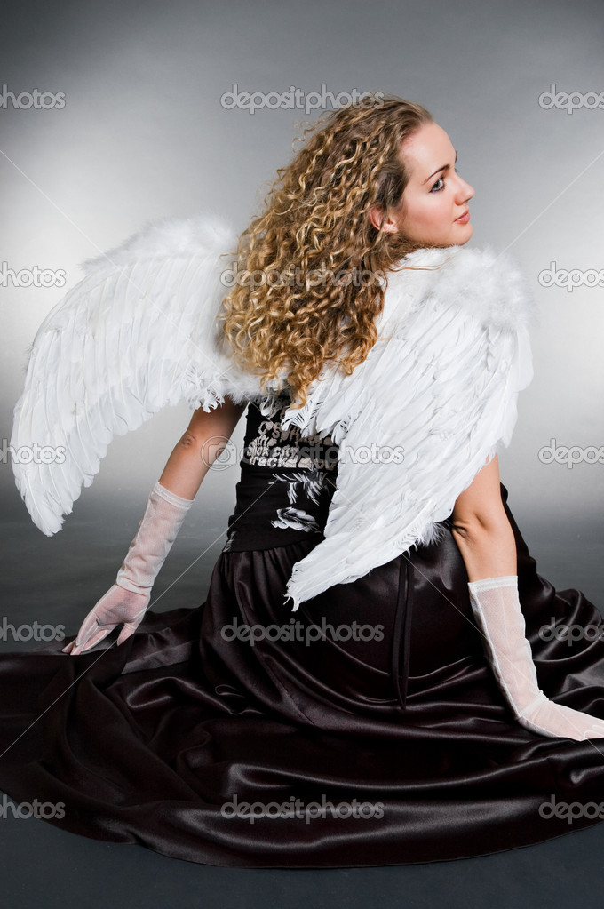 Sweet angel sitting against grey background  Stock Photo #5158401