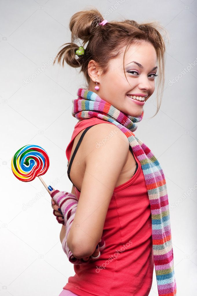 Playful girl with lollipop posing against grey background — Stock Photo #5158623