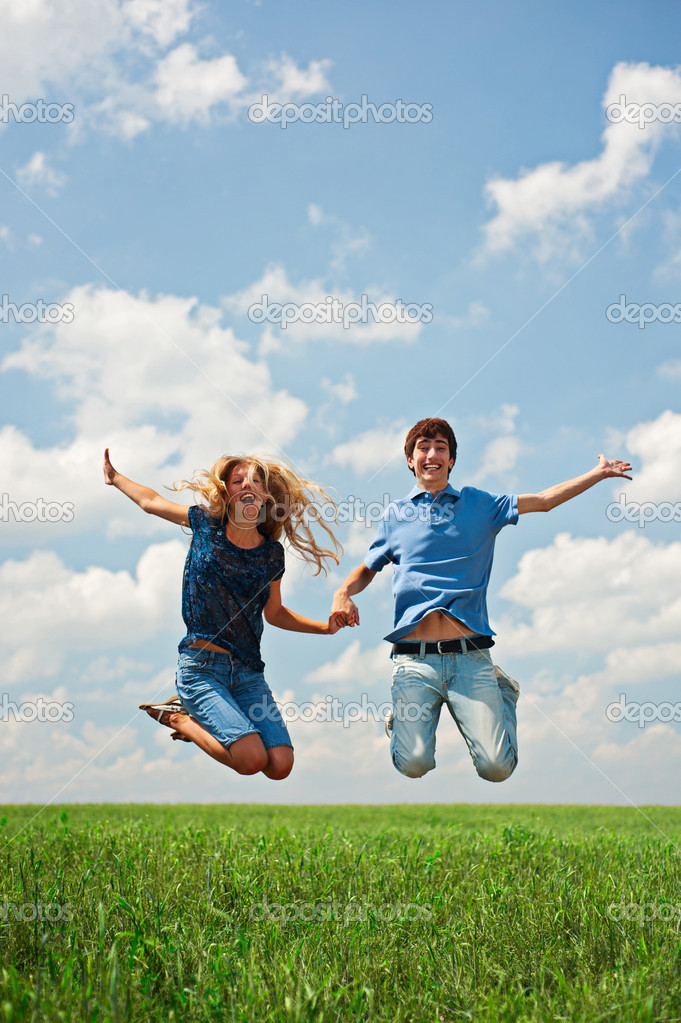 Happy couple jumping on the green field  — Stock Photo #5159148