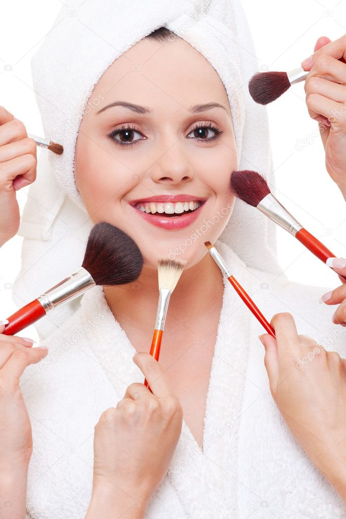Many hands applying make-up to beautiful smiley woman — Stock Photo #5159685