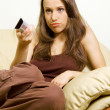 Bored woman watching tv - Stock Photo