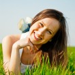Happy healthy woman lying in the grass — Stock Photo