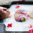 Pretty woman relaxing in milk bath - Stock Photo