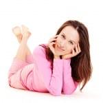 Smiley young girl lying in pink pyjamas — Stock Photo