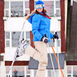 Woman in ski with hotel at the background — Stock Photo