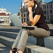 Woman sitting on the stairs with laptop — Stock Photo