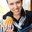 Woman with burger reading book — Stock Photo #5160956