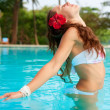 Woman with red flower in the pool — Stock Photo #5160983