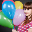 Smiley girl with motley balloons - Foto Stock
