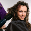 Heirdresser blow-dry hair of client — Stock Photo