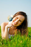 Happy healthy woman lying in the grass — Stockfoto