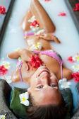 Happy woman taking pleasure in milk bath — Stock Photo