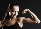 Smiley sportswoman showing her muscles — Stock Photo