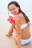 Smiley woman in white swimsuit sitting — Stock Photo