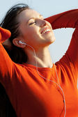 Sunny picture of happy woman listening music — Stock Photo