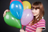 Smiley girl with motley balloons — Stock Photo