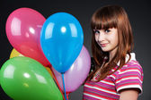 Teenager girl with motley balloons — Stock Photo